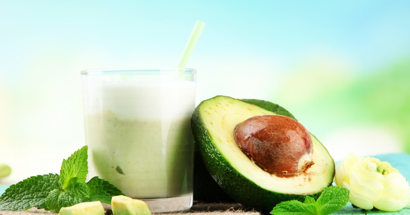 copo com smoothie de abacate cercado por pedaços da fruta