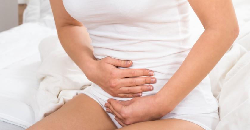 Mulher sofrendo de fortes dores de azia segurando seu estômago