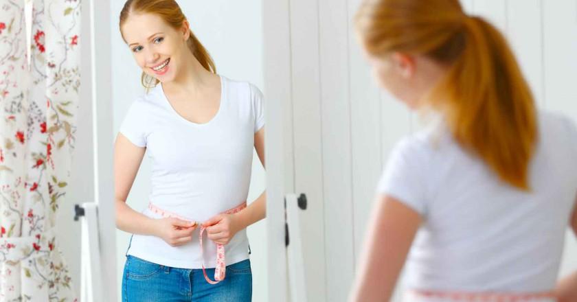mulher que fez redução de estômago tirando as medidas de sua cintura