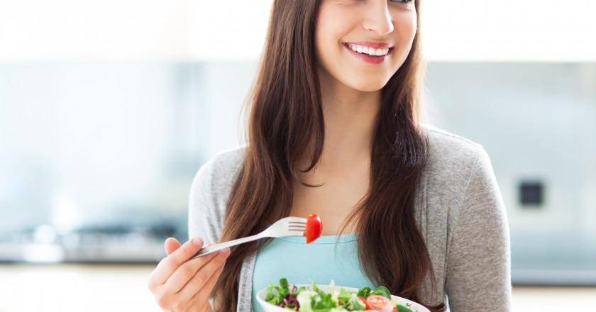 mulher saudável se alimentando e sorrindo