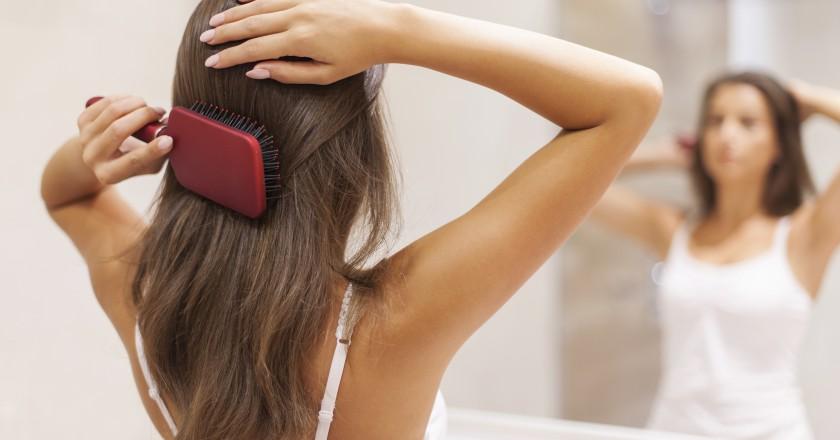 mulher que possui problema de queda de cabelo escovando o cabelo