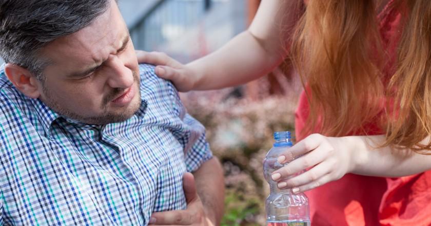 homem de meia idade com azia recebendo ajuda de sua filha