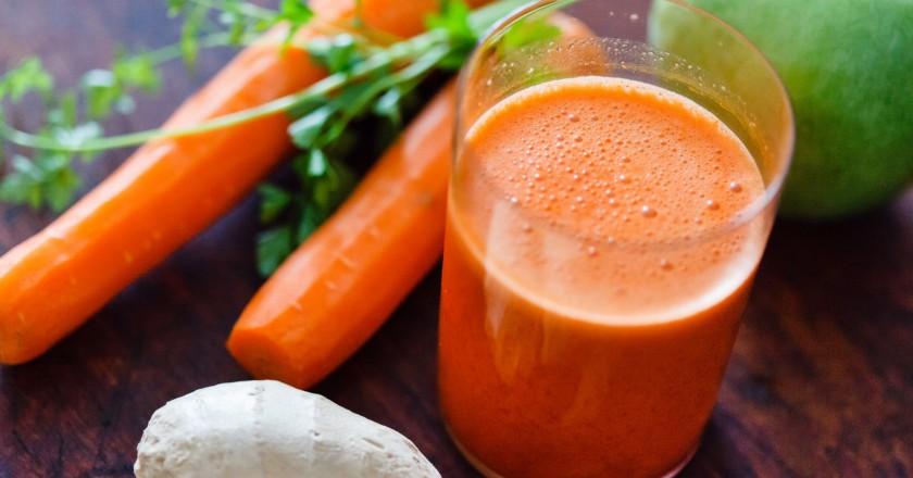 Suco com smoothie detox de cenoura com lima e alguns vegetais crus