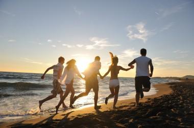 grupo de amigos correndo na praia e se divertindo