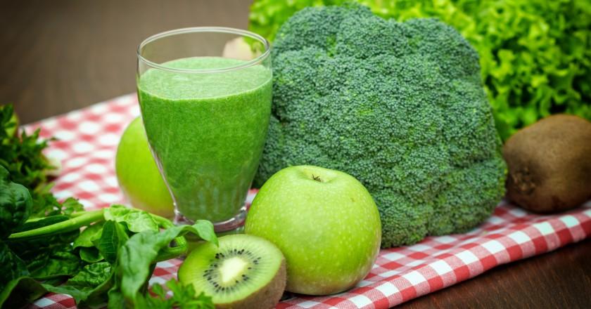 copo com smoothie detox de brócolis ao lado de frutas e outros legumes