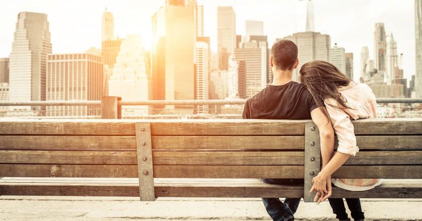jovem casal apaixonado sentado em banco observando a vista