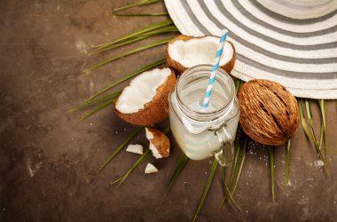 jarra transparente com smoothie de água de coco cercado por cocos
