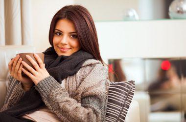 mulher gripada com roupas de frio tomando uma bebida quente