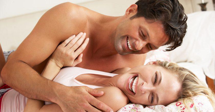 Casal apaixonado sorrindo deitado na cama