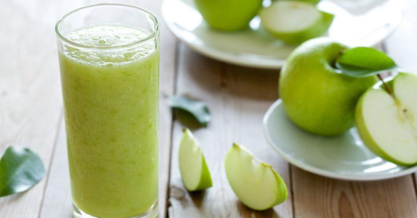 copo com smoothie verde de maça cercado por pedaços da fruta sob uma mesa