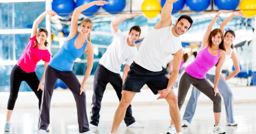 pessoas com as mãos pro alto praticando exercícios físicos para evitar o envelhecimento