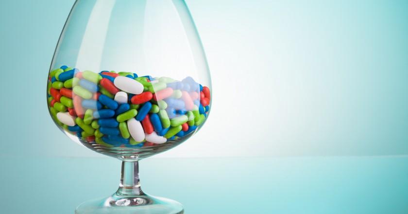 taça cheia de comprimidos e o perigo ao misturara bebidas alcoólicas com remédios