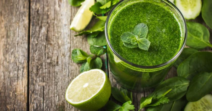 copo com smoothie verde de limão cercado por limões
