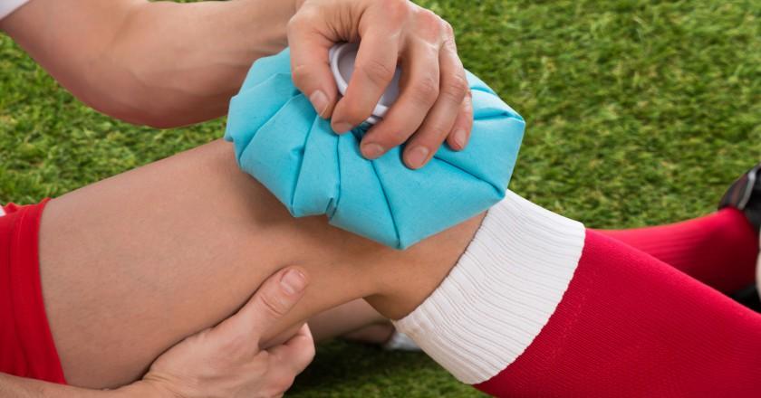 jogador de futebol colocando compressa com gelo no joelho para trata lesão