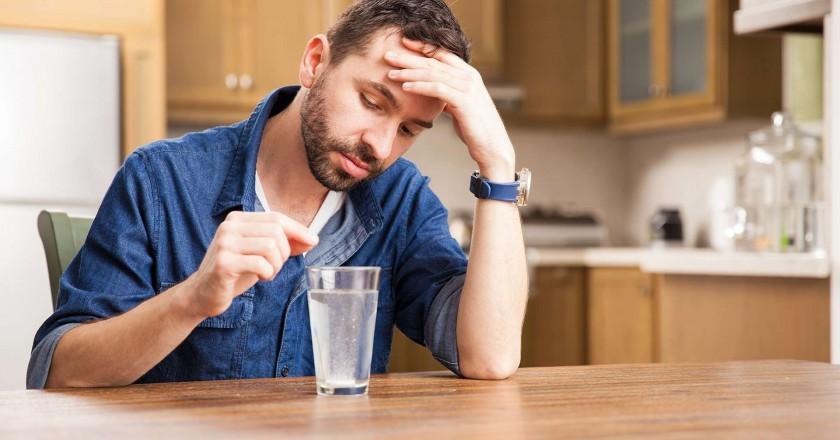 homem sentado em frente a um copo de vidro apoiado sobre a mesa despejando um remédio anti azia