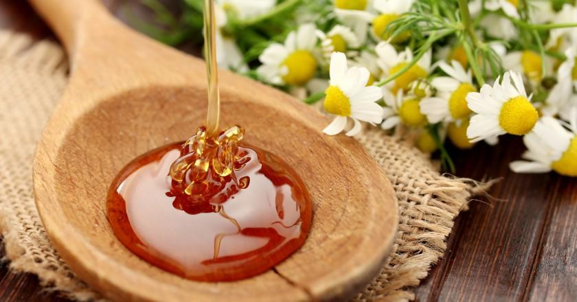 mel sendo despejado em uma colher de madeira para preparar um xarope contra tosse