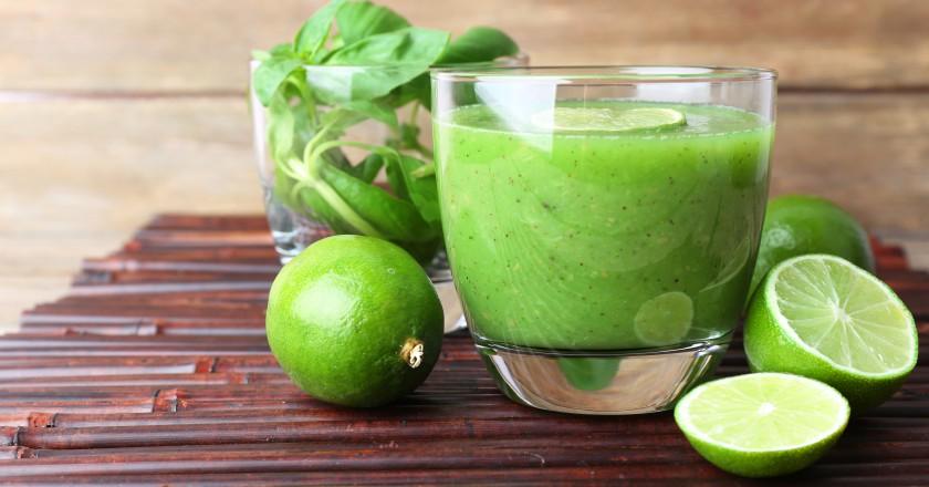 copo com smoothie detox de manjericarão com maçã sob uma mesa de madeira