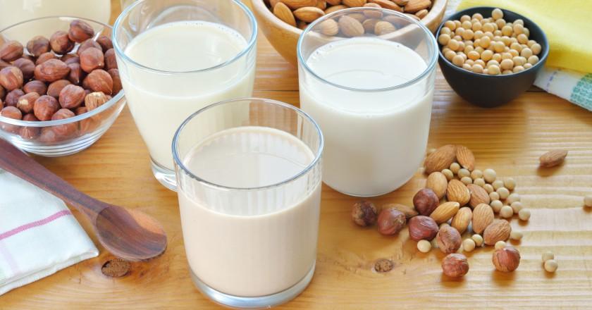 copos sobre uma mesa contendo vários tipos de leite