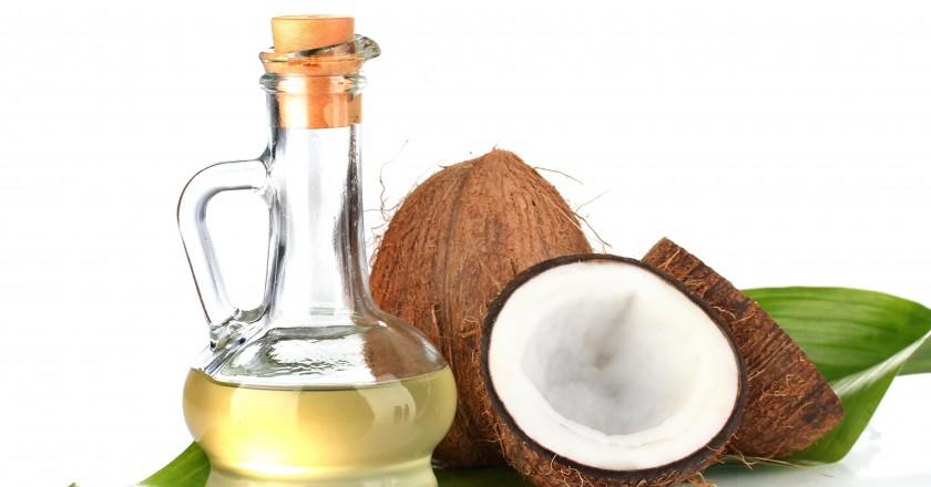 Jarra de vidro com óleo de coco e a fruta