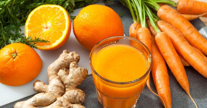 copo com smoothie detox de cenoura com laranja, cenouras e gengibre ao redor apoiados em uma superfície plana