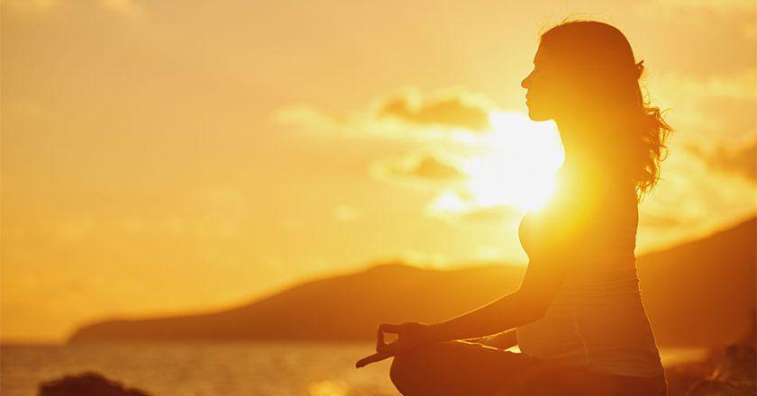 mulher sentada ao ar livre tomando sol e absorvendo vitamina D
